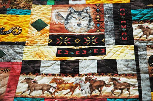 Colorful Quilt Featuring Various Designs, Wolves, and Horses
