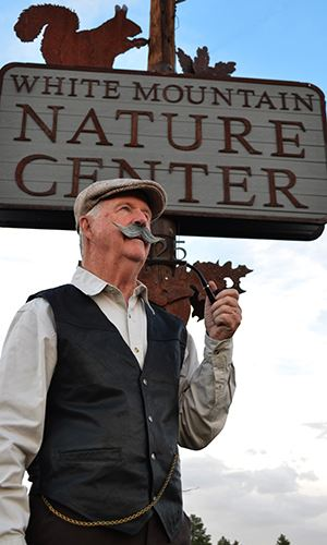 Man in Historical Garb Standing in Front of White Mountain Nature Center Sign